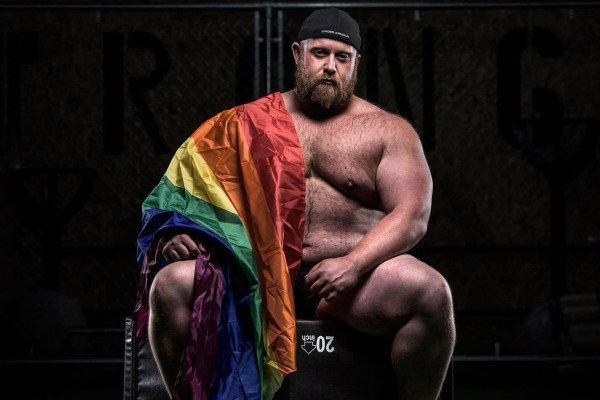 strongman draped in a rainbow flag
