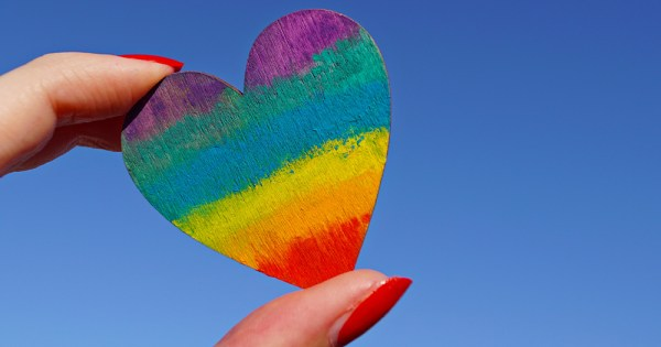 Two fingers with nail polish on squeeze a tiny rainbow coloured heart