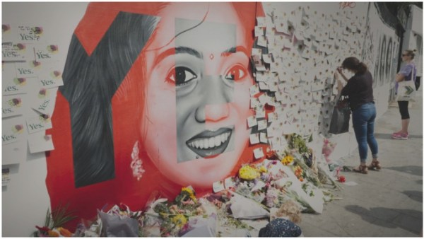 A woman leaves flowers at the painted mural of another woman on a wall