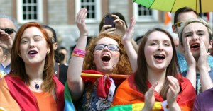 Young people cheering wearing rainbow flag during the marriage equality referendum announcement