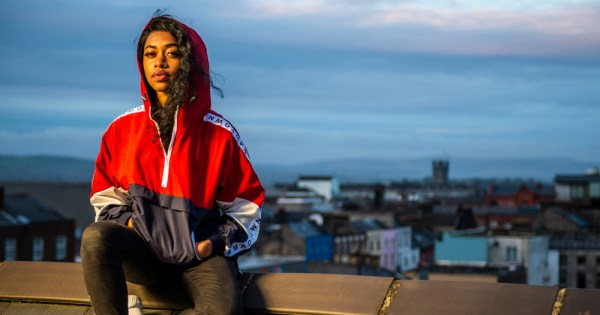 A young woman sits overlooking a city, her hood up, hair blowing from it