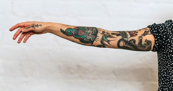A tattooed female arm reaches out