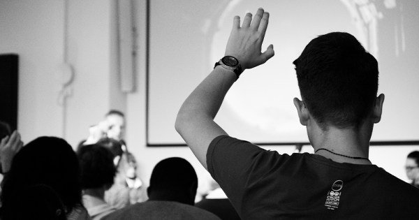 A young man seen from behind raises his hand in a crowded classroom
