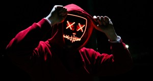 A hooded figure wearing a mask with lighted x's