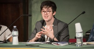 A young woman with short hair and glasses speaks at a press conference