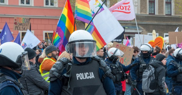 Police in Poland stand in front of a crowd waving rainbow flags