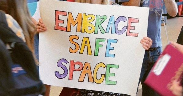 """LGBT+ safe spaces - hands holding a sign that reads """"Embrace safe space"""""""