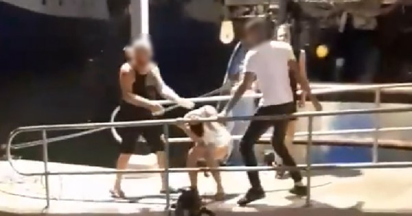man tries to protect other man from being attacked by man at Jaffa Port in Israel