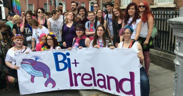 A group of people gathered around a Bi Ireland banner