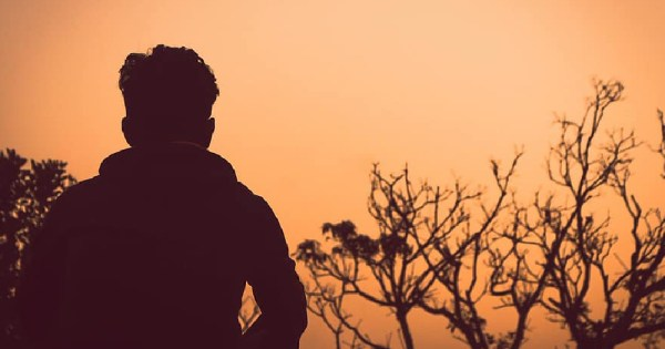 LGBT+ homelessness Ireland silhouette of young person against an orange sky with leaveless trees in background