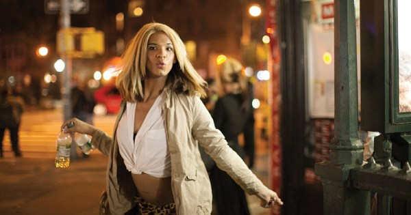 A young Black trans woman twirls on a city street at night
