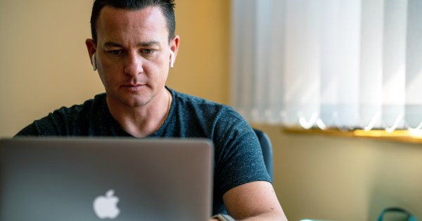 Man looking at his laptop. Amach LGBT Galway is organising free mental health workshops