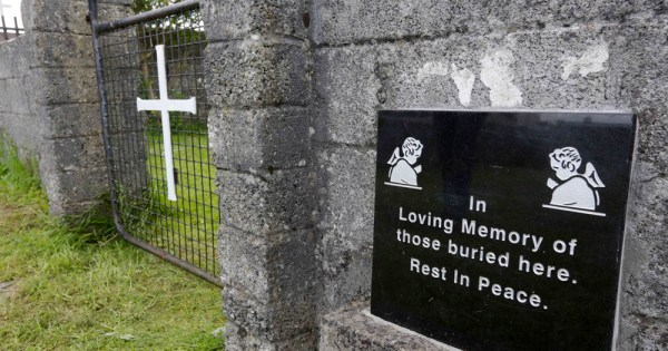 A picture of the mother and baby home memorial site at Tuam, concrete wall and wire gate
