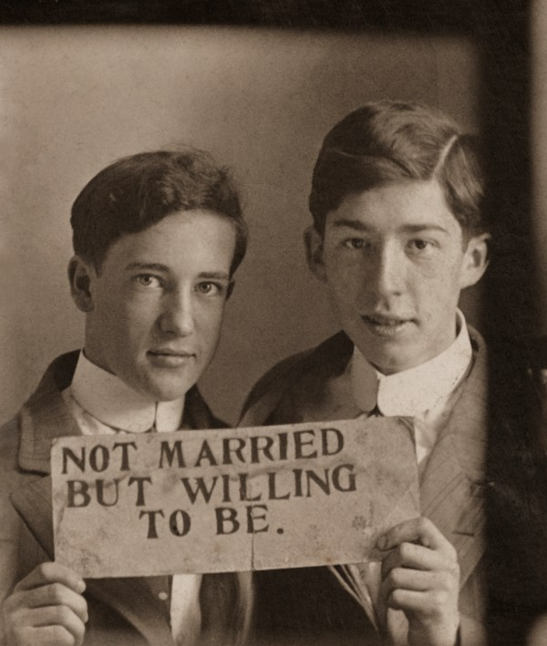 """Two men in suits holding up a sign, """"Not married but willing to be"""""""