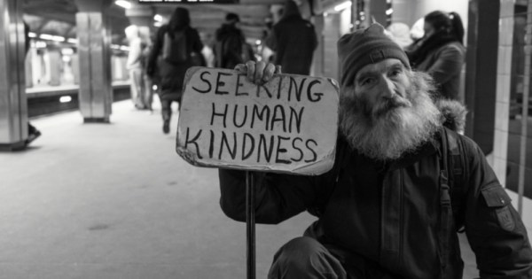 """a homeless man holding a sign that says """"seeking human kindness"""", the world is getting kinder."""