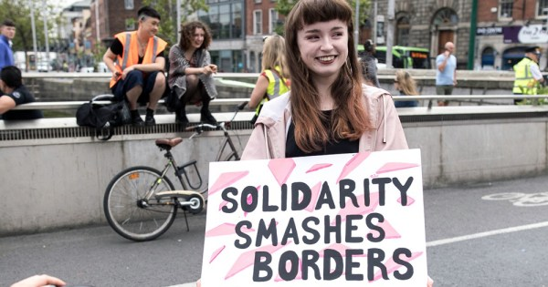 Trans Solidarity: Person holding a sign that says Solidarity Smashes borders