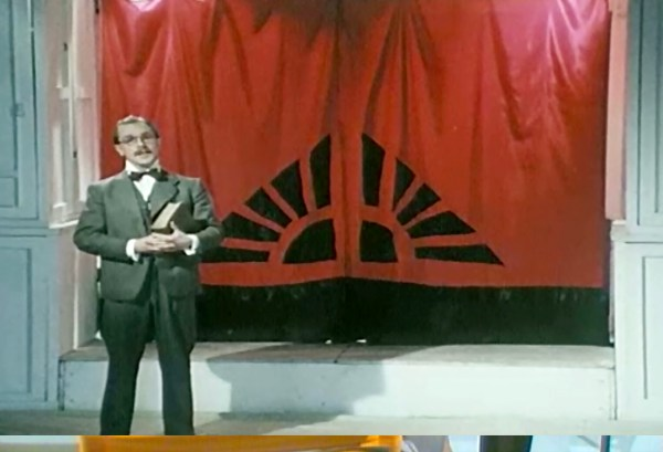 A man stands on a stage with a large book in his arms and a red curtain behind him.