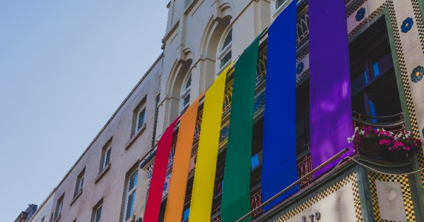Rainbow flags hanging off the side of a building