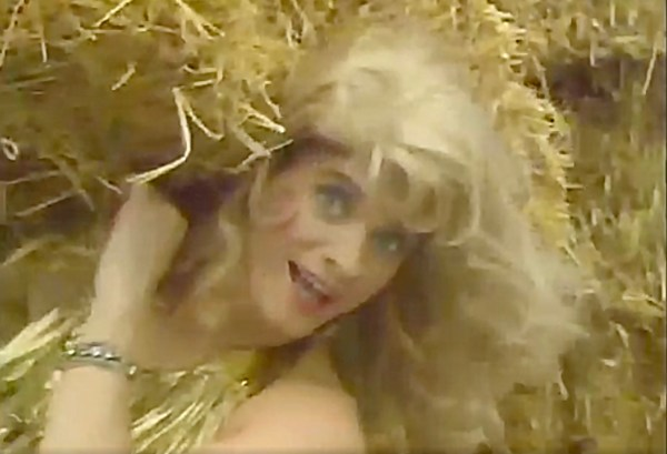 A drag queen smiles at the camera while lifting some hay.