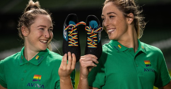 Two smiling sportswomen holding up boots with rainbow laces