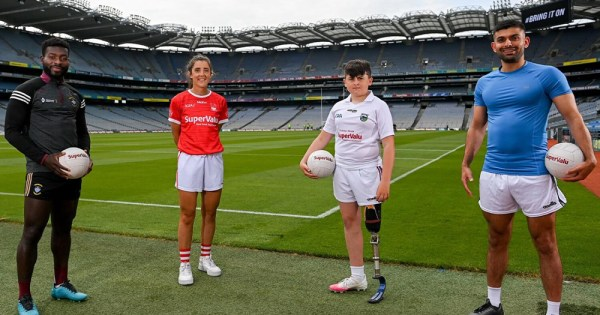 Four diverse people standing on a GAA pitch
