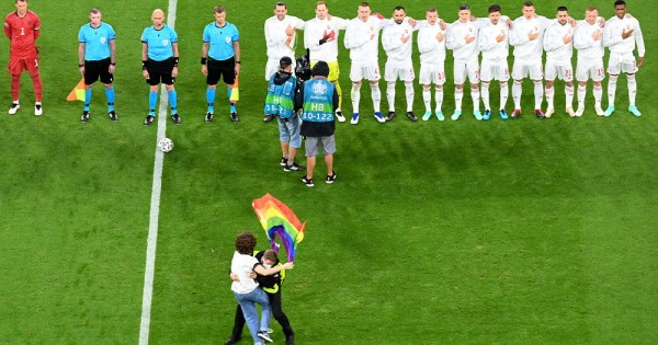 A protestor invading a football match with a Pride flag gets stopped by security
