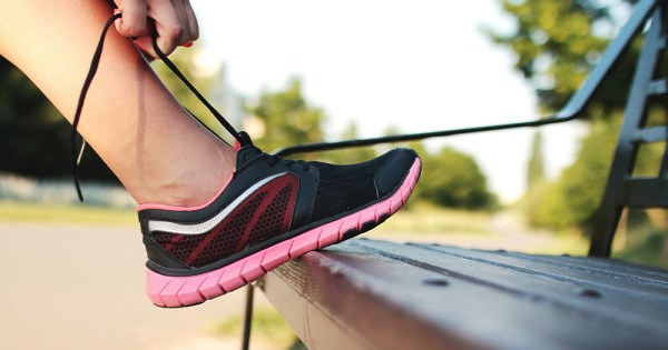 A hand laces up a pink running shoe