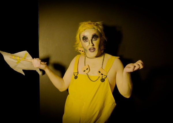 A drag artist stares at the viewer with arms up dressed in yellow