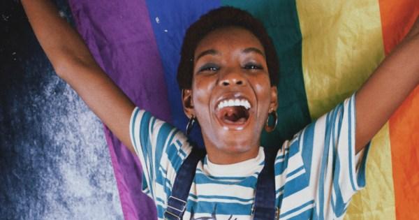 A joyous woman holding up a rainbow coloured fabric