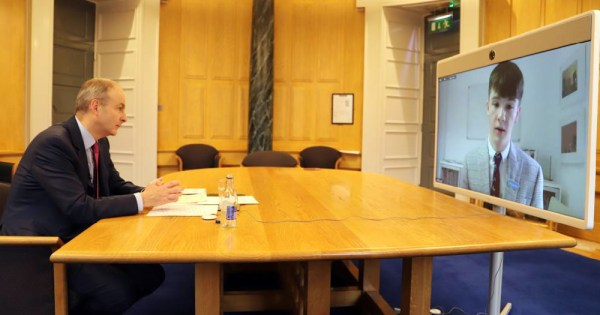 A man in a board room talking to a teenage boy on zoom