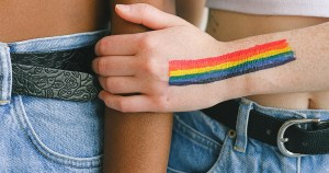 A hand with a rainbow painted on it holds another arm