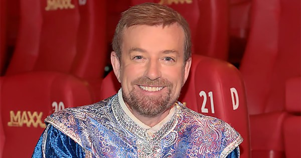 A headshot of Alan Hughes, wearing his Sammy Sausages costume, in the cinema with red seats behind him