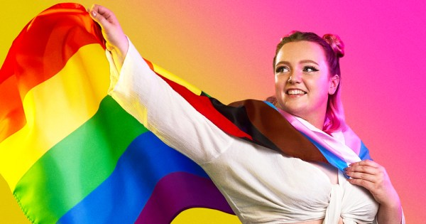 A smiling young woman wearing a Pride flag like a cape
