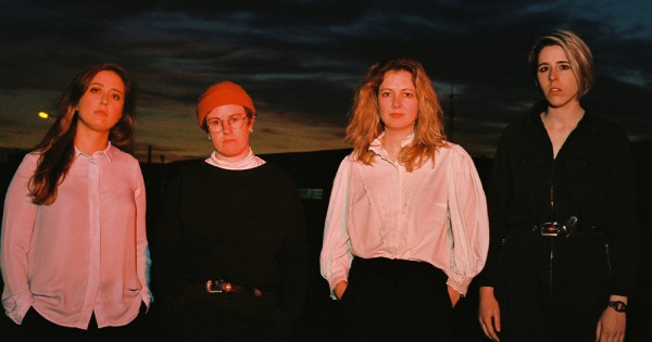 Four women in a moody pose at night