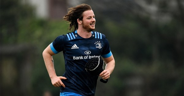 A smiling long haired man in rugby gear running