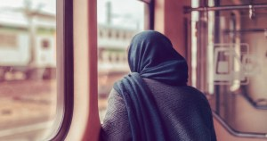 an image of a woman staring out a window wearing a hijab