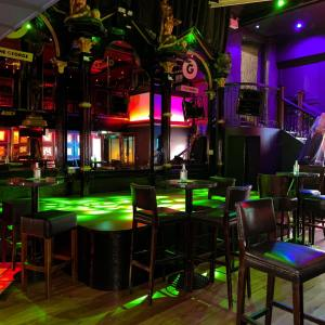 Empty interior of The George, colourfully lit stage surrounded by vacant chairs and tables