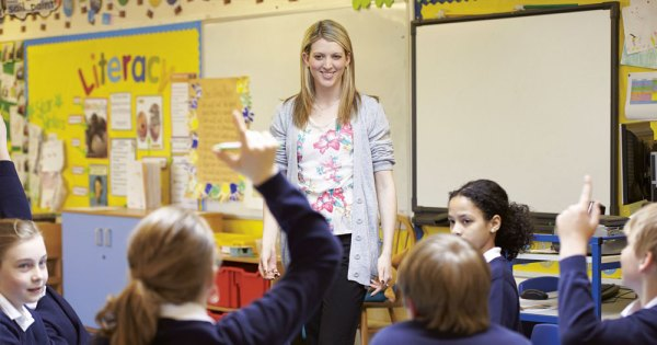 A smiling female teacher stands at the top of a classroom full of engaged students
