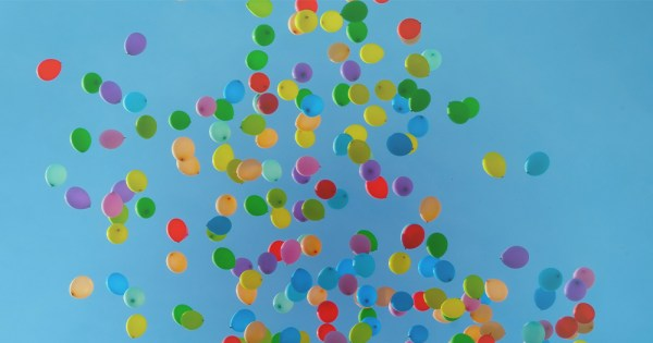 Multicoloured balloons floating away into the sky