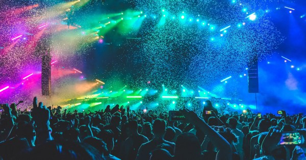 People at a pop music concert with colourful lights on stage.