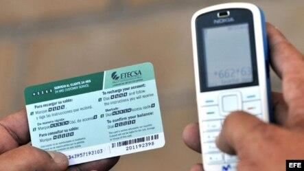 Una persona recarga un teléfono celular con una tarjeta prepago de ETECSA