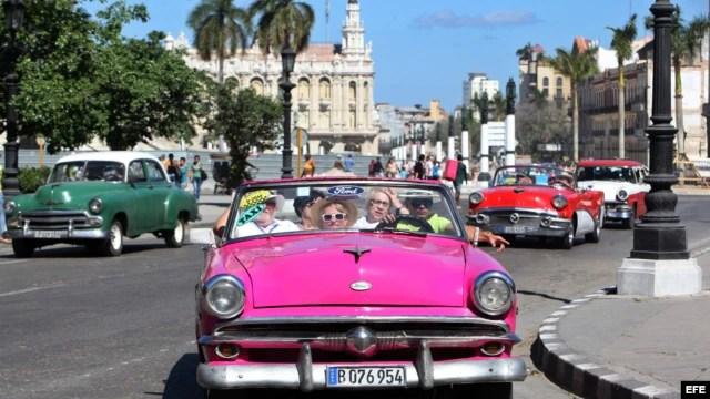 Turistas pasean por La Habana en un auto clásico.