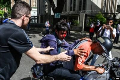 Un grupo de manifestantes ayuda a un compañero herido durante una marcha antigubernamental en Caracas.
