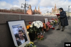 Russia -- A woman lays flowers at the place where Boris Nemtsov was killed before a memorial march for Nemtsov to mark the second anniversary of his murder, in Moscow, February 26, 2017