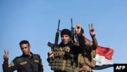 Iraqi forces raise the victory sign east of Mosul