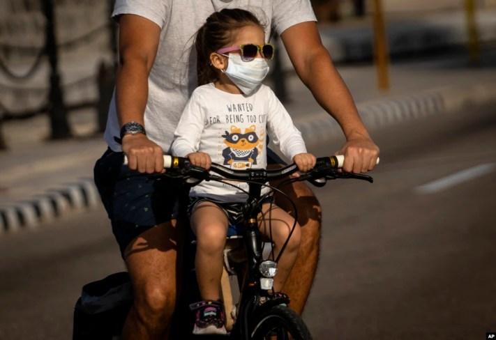Una niña transportada en bicicleta usa un nasobuco para evitar el contagio del coronavirus, en La Habana.