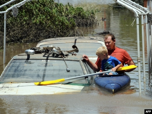 A man and his son kayak past flooded cars in Bundaberg, Australia, on December 31.
