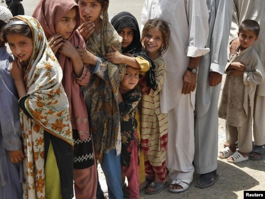 Children stand in line at a distribution center in Kurram.