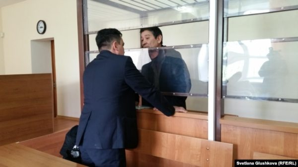 Подсудимый Амин Елеусинов, лидер профсоюза нефтесервисного предприятия OCC, разговаривает со своим адвокатом Толегеном Шаиковым. Астана , 15 мая 2017 года.