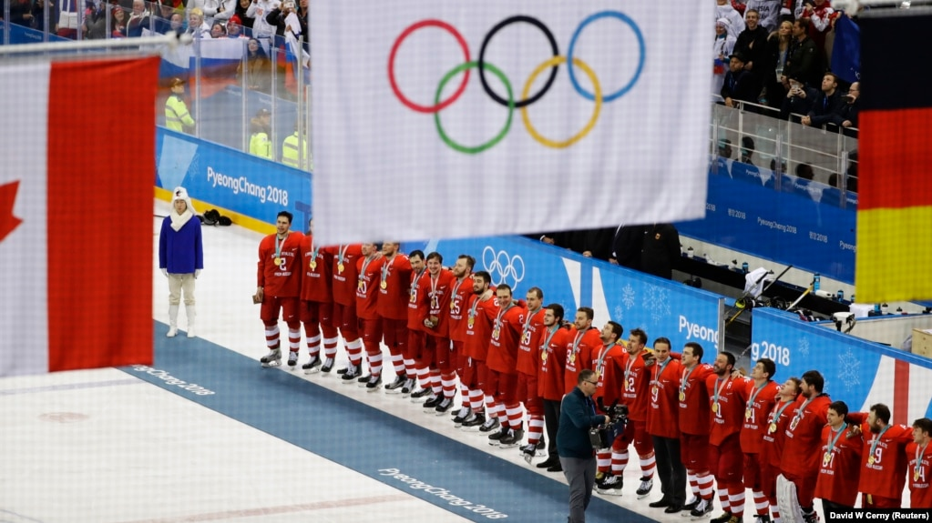 Olympic ice hockey players from Russia wear their gold medals under the Olympic flag during the 2018 Winter Olympics in Pyeongchang.